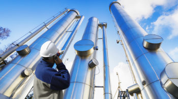 oil-worker, engineer with large oil and gas pipes, pipelines, sl